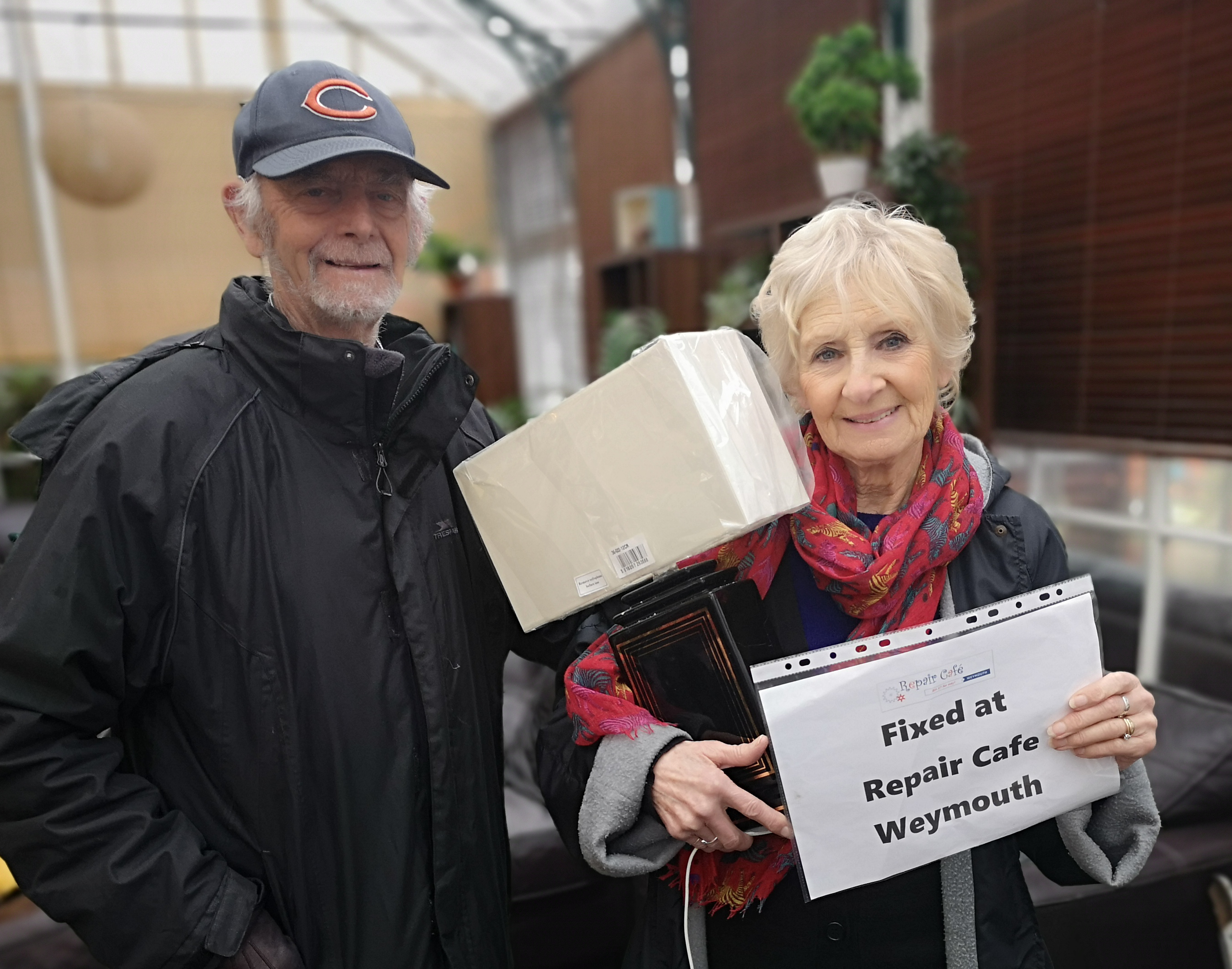 Two customers with a repaired lamp